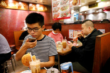 """Student leader Joshua Wong takes photos as he eats a traditional pineapple bun with butter ahead of an appeal verdict on charges related to the 2014 pro-democracy protests, also known as """"Occupy Central"""", at Mongkok, Hong Kong"""