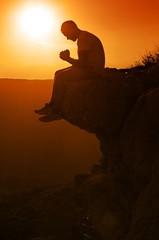 Praying Man Sitting on Rock