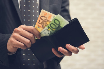 Businessman opening wallet and taking out some money, Euro currency
