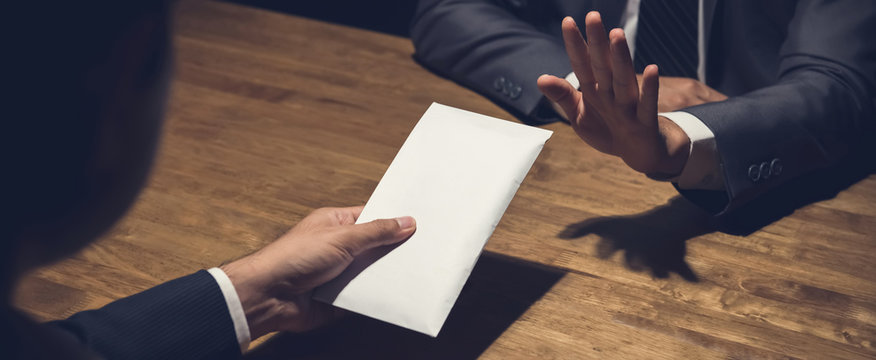 Businessman rejecting money in white envelope offered by his partner in the dark, anti bribery concept