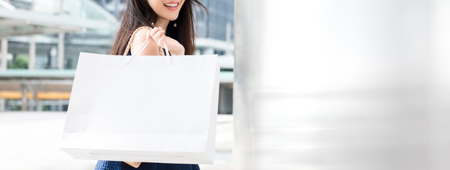 Smiling young woman carrying shopping bag in the city, panoramic banner
