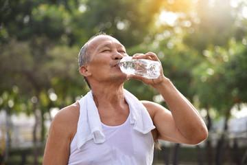 Asian senior male drinking water.