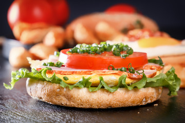 Sandwich with fried egg, bacon, tomato, greens. Breakfast with fried potatoes and mushrooms. Black background
