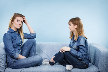 Two serious women friends talking on sofa
