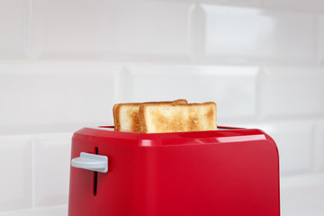 Red toaster with bread slices on white background
