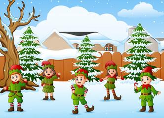 Happy kid wearing elf costume in the snowing village