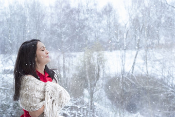 Brunette woman enjoying the snowfall - Attractive young woman with long dark hair, in a red dress, covered by a handmade shawl, with her eyes closed, enjoying the snowfall.