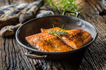 Salmon. Two juicy salmon steaks in roast pan with herb decoration on rustic oak table