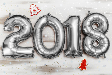 Bright metallic silver balloons figures 2018, Christmas, New Year Balloon with glitter stars on white wood table background