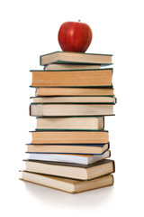 Book tower with a red apple isolated on white