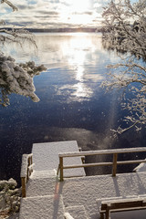 Beautiful view of Lake Pyhäjärvi, snowy trees and pier and snow falling from trees on a sunny day in the winter in Tampere, Finland.