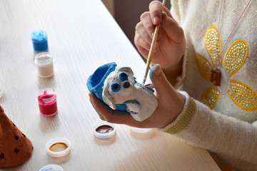 Making toys, paints a pottery clay dog figure with gouache. Indoors creative leisure for children. Supporting creativity, learning by doing, DIY project, hand craft. Master class of art.
