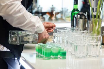barman pours cocktails