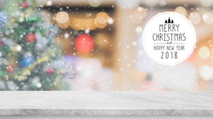 White marble stone table top on blur with bokeh Christmas tree background with snowfall - can be used for display or montage your products.