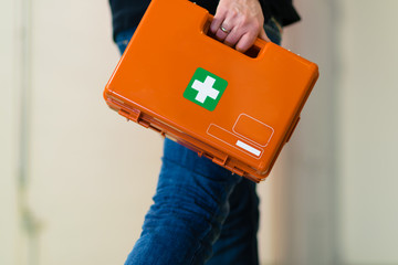 Man with first aid kit runs to help