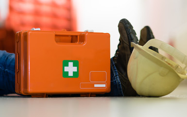 Man lying on the ground after a work accident and a first aid kit stands next to him