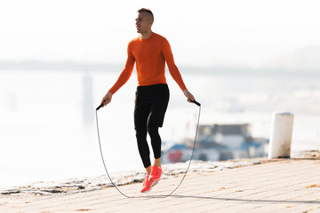 Handsome young man wearing sportswear and  skipping rope at quay during autumn