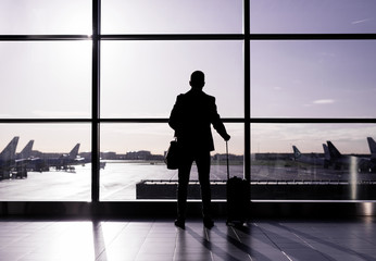 Man standing in airport, silhouette against glass wall