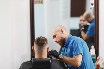 Male professional hairdresser serving client, shaving thick big beard straight razor. Ginger handsome stylish young man with short hair getting trendy haircut, black cape. Light white barber shop room