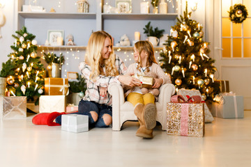 Festive image of mother and daughter sitting on chair in background of Christmas tree