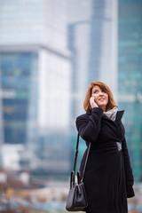 Photo of girl in black coat talking on phone