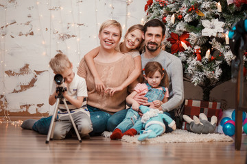 New Year's image of family sitting at decorated Christmas tree