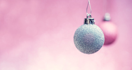 Picture of New Year's pink and gray balls on empty pink background.