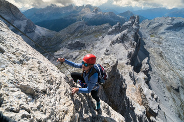 attractive young female climber on a steep Via Ferrata in the Italian Dolomites with a great view