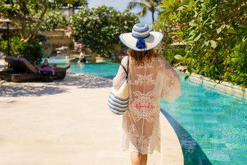 Woman walking near swimming pools in tropical luxury resort