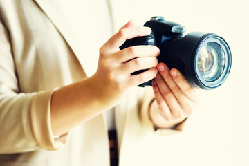Girl hands holding photo camera, white background, copy space. Travel and shoot concept