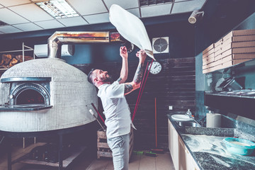 Canvas Prints Pizzeria Bearded pizzaiolo chef lunching dough into air