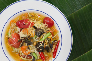 Papaya salad mix with salted crab (Som Tum) in white dish on banana leaf Thai food