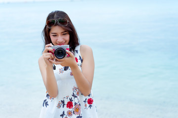 Asian woman taking photo with camera mirrorless at beach,Lifestyle hipster and travel relaxation,rest in summer season vacation concept, Selective camera focus