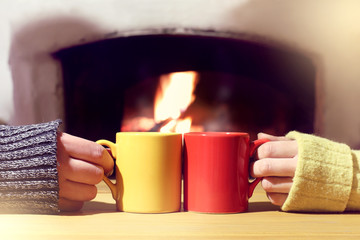 cozy evening for winter vacations together/ red and yellow mug in the hands of a couple of people basking at the fireplace