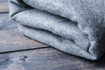 Grey blanket on a wooden background