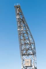 metal port crane with three hooks and blue sky