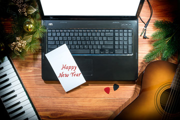 Happy New Year - Musical Christmas background with Acoustic guitar, musical keyboard, laptop on a wooden table