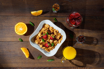 Cereal, morning breakfast, corn flakes, raisins, almonds, mint leaves, orange juice, strawberry, top view, on a dark wooden background, flat lay. The concept of healthy, proper nutrition, ditox.