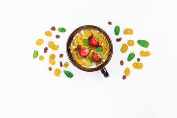 Cereal, morning breakfast, corn flakes, raisins, almonds, mint leaves, strawberry, top view, white background, flat lay. The concept of healthy, proper nutrition, ditox.