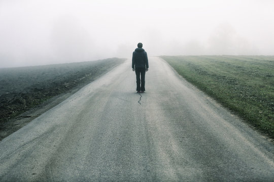 Man standing alone on rural foggy and misty asphalt road.