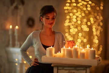 Woman with candles, fireplace, christmas lights.