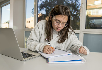 female young student teenager girl studying with computer laptop writing on notepad happy and confident preparing exam at library