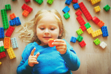 cute little girl play with plastic blocks