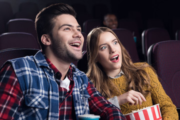 young smiling couple with popcorn watching movie in cinema