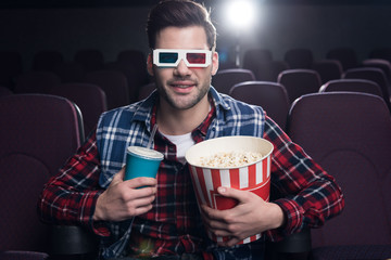 handsome man in 3d glasses with popcorn and soda watching movie in cinema