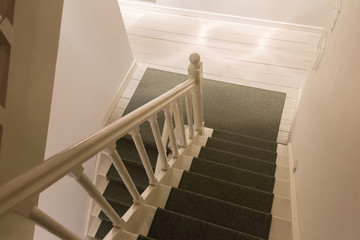 White wooden stairs with green carpet
