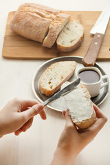 The girl spreads soft curds on bread. Sandwich of fresh ciabatta with butter. Delicious breakfast .