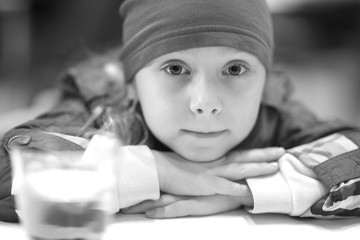 Monochrome portrait of a little girl at a table in a cafe closeup