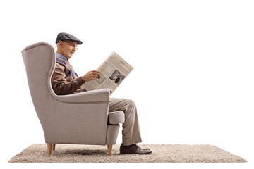 Senior seated in an armchair reading a newspaper