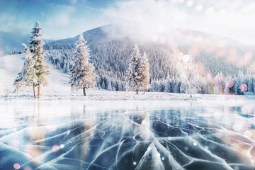Blue ice and cracks on the surface of the ice. Frozen lake in winter mountains. It is snowing. The hills of pines. Winter. Carpathian Ukraine Europe